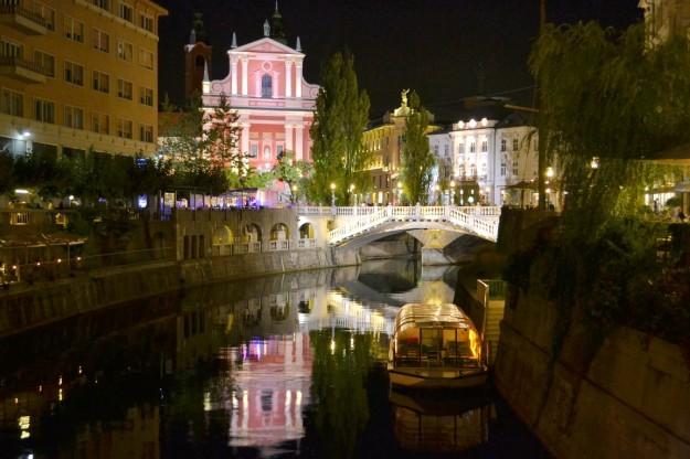 La iluminada noche sobre el Río Ljubljanica, con el triple puente