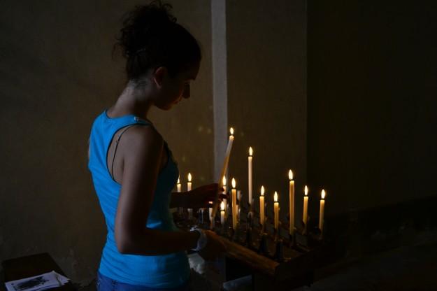 Jani encendiendo una vela en una pequeña capillita de Volterra
