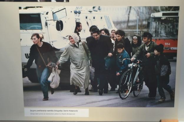Los civiles cruzan la Avenida de Francotiradores refugiándose en un camión blindado de la ONU. Foto en el Museo de Historia de Sarajevo