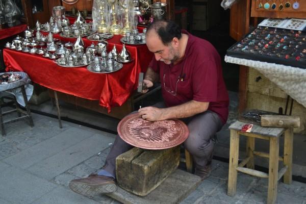 Algunos sí que trabajan duro, como este hombre grabando un plato de bronce