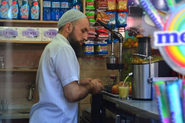 Un vendedor musulmán exprime jugos afuera del Grand Bazaar