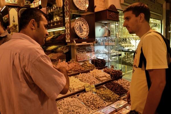 Un empleado convenciendo a un turista de que compre sus productos