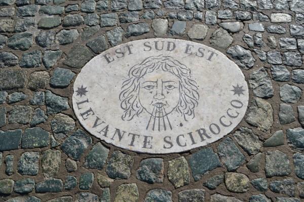 Bajorelieves de la Piazza San Pietro, indicando los puntos cardinales
