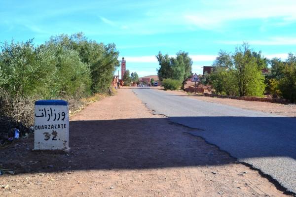 Paisaje rutero del sur de Marruecos, con un cartel indicando la cercanía a la ciudad de Ouarzazate
