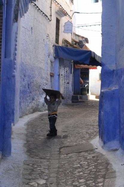 Un niño llevando un cartón por la medina, se da vuelta y se nos queda mirando...