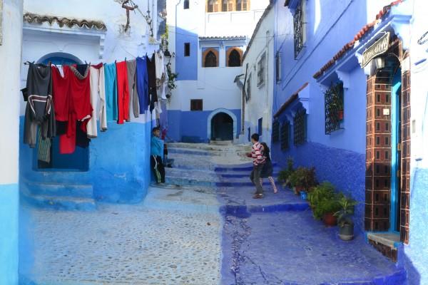 Unos niños juegan en la medina de Chauen. El contraste con el fondo azulado resulta del todo curioso